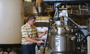 """Dennis Harstad, Prairie AquaTech's vice president of operations and general manager, works with machines that produce enzymes for applying to soybean meal to make it higher in protein and more digestible for aquaculture. He thinks the market will be """"phenomenal"""" and as big as ethanol for this region. Photo taken July 15, 2016 in Brookings, S.D. (Forum News Service/Agweek/Mikkel Pates)"""